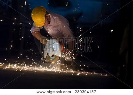 Low Light Image Of Worker Ware Yellow Helmet Kneel Use Electric Steel Cutter Machine. He Has A Hard