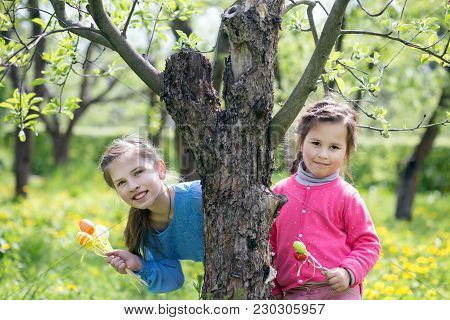 Two Smiling Children Peeking Out From Behind A Tree With Easter Eggs In Hands