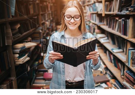 Bright And Warm Picture Of Clever Student Reading A Book. Girl Is Smiling And Continue To Read Book