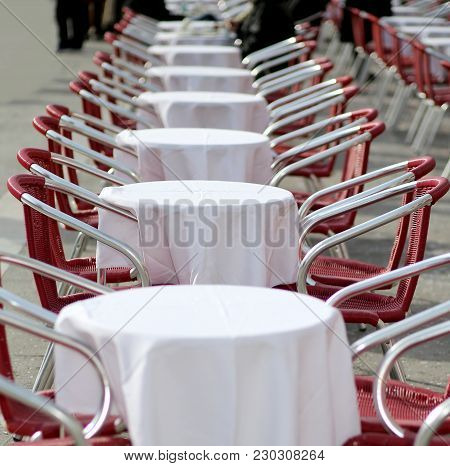 Tables And Red Chairs In An Alfresco Cafe In The European City