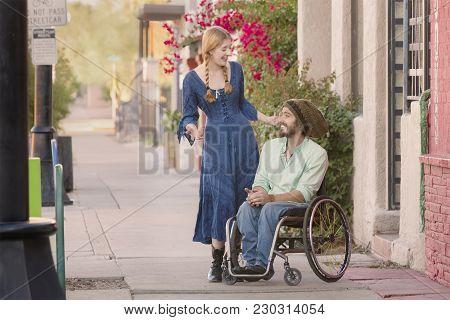 Woman Having A Conversation With Friend In Wheelchair On Sidewalk