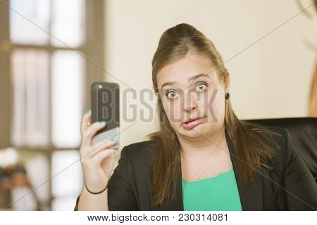 Young Creative Professional Woman Reacting To Phone Content With A Funny Face