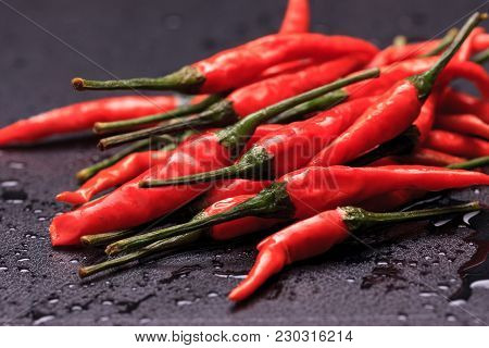 Close Up Of Spicy Red Peppers. A Close Up Photo Of Wet Spicy Red Peppers On A Black Background.