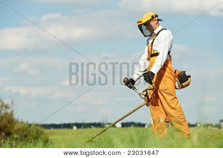 Young worker with power tool string lawn trimmer mower cutting grass near road