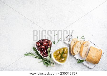 Ciabatta Bread, Olives, Oil, Herbs On White Background. Mediterranean Snacks. Top View, Copy Space