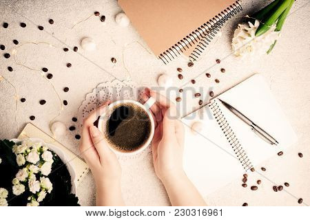 Female Hands Holding Coffee Cup. Coffee, Flowers, Notebooks And Led Lights, Cozy Weekend Concept, To