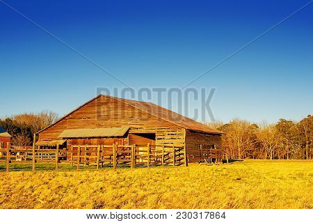 An old wooden country barn and corral in beautiful blue and gold tones in North Carolina, USA.