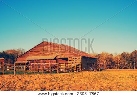 A rustic old wooden barn and corral in the country in North Carolina, USA.