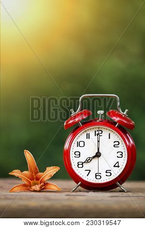 Daylight Savings, Spring Forward Concept - Red Alarm Clock And Flower - Vertical Image With Blank, C