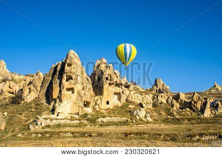 Hot Air Balloon Overhanging The Ancient Dwellings Of Cappadocia, Turkey