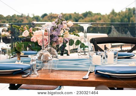 Romantic Wedding Or Another Catered Event Table Setting, Flowers, White Plates, Candles, Blue Napkin