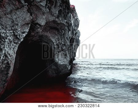 Dark Cave On The Beach And Water Of Red Color