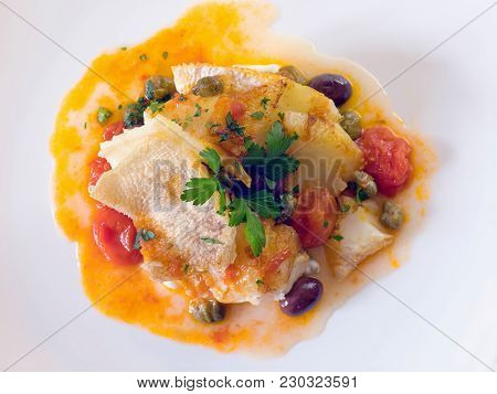Grilled Cod With The Addition Of Tomato Olives And Capers.