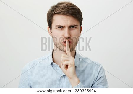 Do Not Cause Noise, Shh. Portrait Of Strict Serious Handsome Guy In Casual Blue Shirt Holding Index