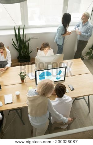 Senior And Young Employees Work In Office Together, Older Executives Training Colleagues, Corporate