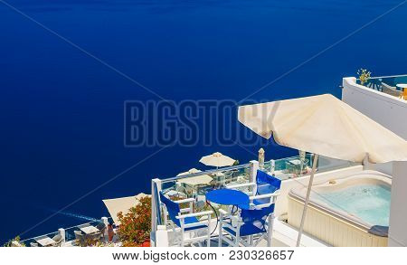 Chairs And Tables Beside The Pool Of The Hotel Overlooking The Sea In Santorini, Greece