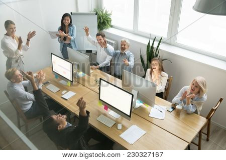 Excited Diverse Team Celebrating Corporate Business Success Applauding African Coworker Congratulati