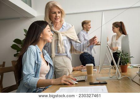 Aged Female Mentor Training Young Asian Intern Explaining Computer Work, Senior Friendly Executive T