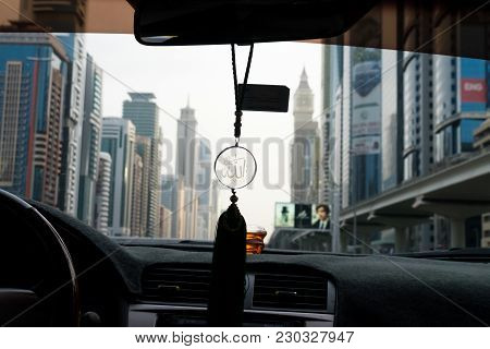 Allah Symbol Hanging In A Car With The City Of Dubai On The Background