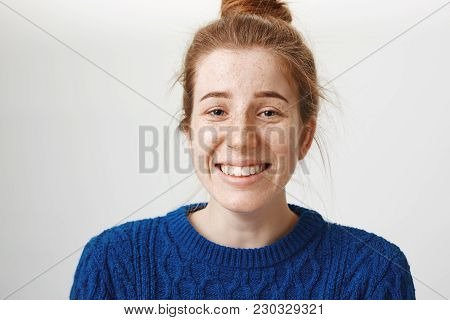 Close-up Portrait Of Good-looking Girl With Freckles And Natural Red Hair Smiling Nervously And Chuc