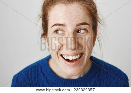 Close-up Shot Of Attractive Young Caucasian Female With Red Hair And Freckles Laughing And Looking A