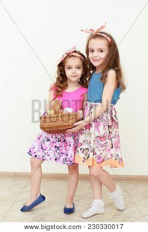 Portrait Of Little Girls Holding Easter Basket Of Painted Eggs. Portrait Of Easter Little Sisters Ho