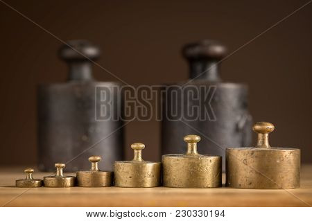 Old Iron 1kg Weights And Smaller Brass Weights For A Kitchen Scale Standing On A Table