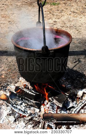 A Cauldron Over A Fire, Smoking Over Smouldering Wood.