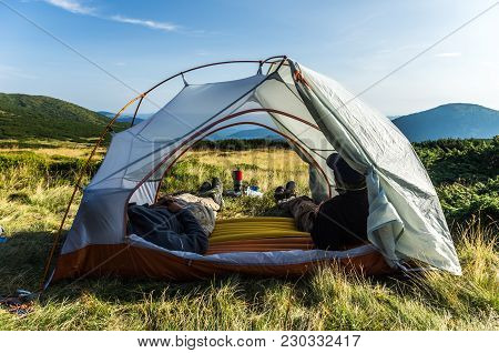 Two People In A Tent. View Of The Landscape Through A Tourist Tent. Tent And Tourist Equipment.