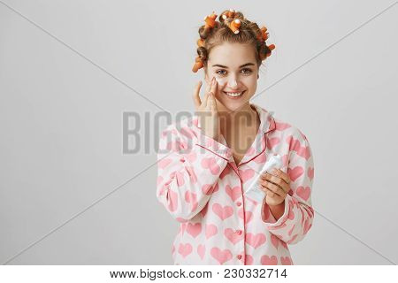 Making skin beautiful. Indoor shot of cute slender female in hair curlers and pyjamas holding facial cream and wiping it on face, smiling broadly while standing over gray background. Copy space poster