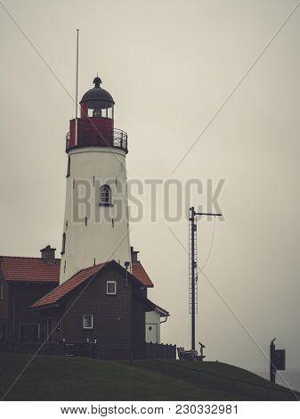 Lighthouse Of Urk, Netherlands On A Misty And Rainy Winter Day.