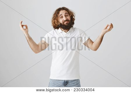 Attractive And Friendly Eastern Guy With Beard And Curly Hair Trying New Meditation Method Standing