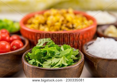 Chopped Cilantro In Wooden Bowl With Ingredients For Mexican Street Corn Salad