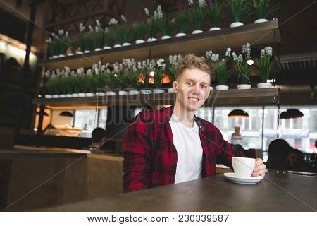 Positive Young Man Sits In A Cafe With A Cup Of Coffee And Smiles. Coffee In The Cafe.