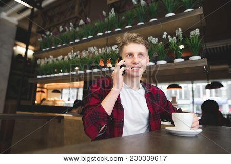A Student Talks By Phone In The Cafe And Smiles. A Young Man Drinks Coffee And Talks Over The Phone.