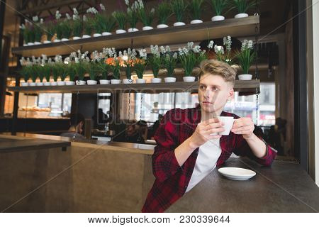 A Thoughtful, Handsome Young Man Sitting In A Cafe, Drinking Coffee And Looking Away. The Student Dr