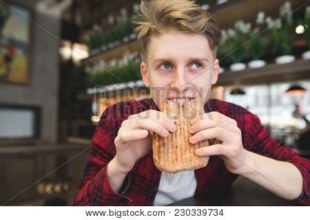 A Beautiful Young Man Eats A Panini Sandwich In A Cozy Cafe. Funny Student Bites Sandwich. Lunch At