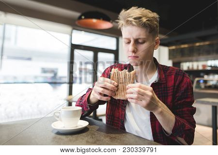 A Handsome Young Man With An Appetite Looking At A Sandwich In His Hands While Lunch In A Cozy Cafe.