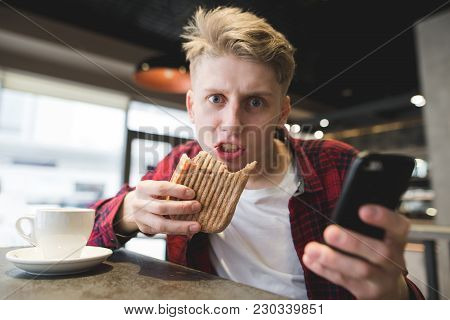 A Crazy Student Eats At A Cafe. A Funny Young Man Eats A Panini Sandwich, Holds The Phone In His Arm