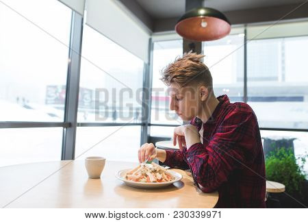 A Student Eats A Salad At A Restaurant Near The Window. Young Man Dishes With Salad In A Cafe.