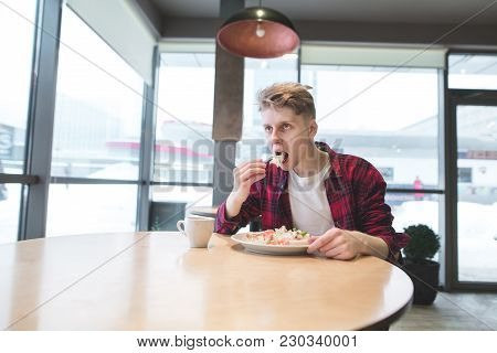 A Young Man In A Red Shirt Eats A Salad In A Cafe Near The Window. A Student Eats Corsin Food In A C