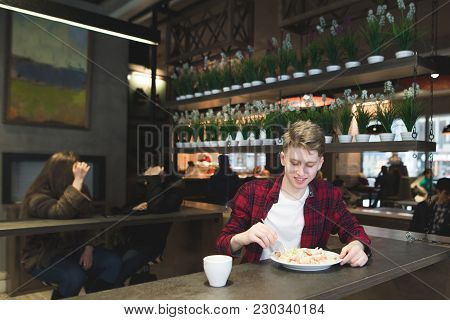 A Young Student In A Red Shirt Eats A Salad In A Cozy Cafe And Looks At The Camera. A Student Eats I