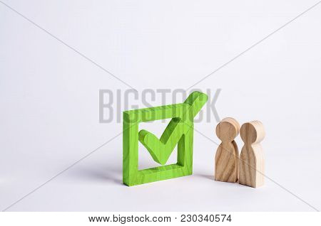 Two Wooden Human Figures Stand Together Next To A Green Tick In The Box. The Concept Of Elections An
