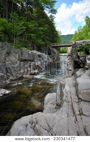 A Footbridge Going Over A River In The White Mountains In New Hampshire.