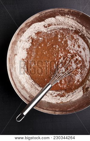 Bowl Of Chocolate Dough And Whisk On Black