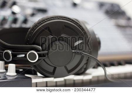 Studio Headphones On The Background Of Audio Equipment.