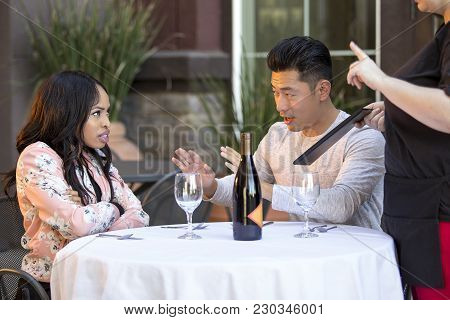 Rude Girlfriend Complaining To A Waitress In A Restaurant With An Embarrassed Boyfriend Trying To Ca