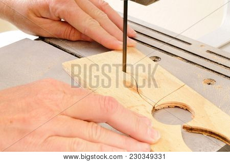 Closeup of a womans hands working with a bandsaw to cut an intricate shape in a piece of plywood
