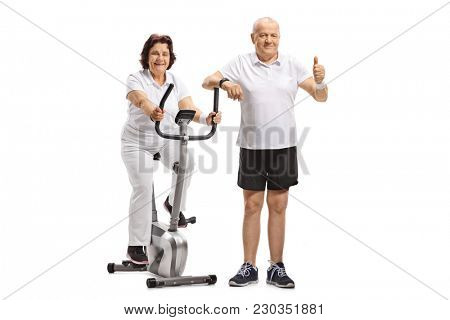 Elderly woman riding an exercise bike with an elderly man making a thumb up gesture isolated on white background