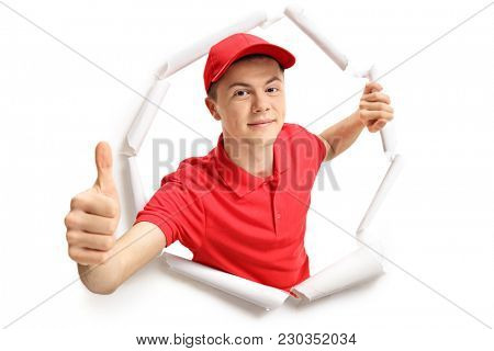 Teenage delivery boy breaking through paper and making a thumb up gesture